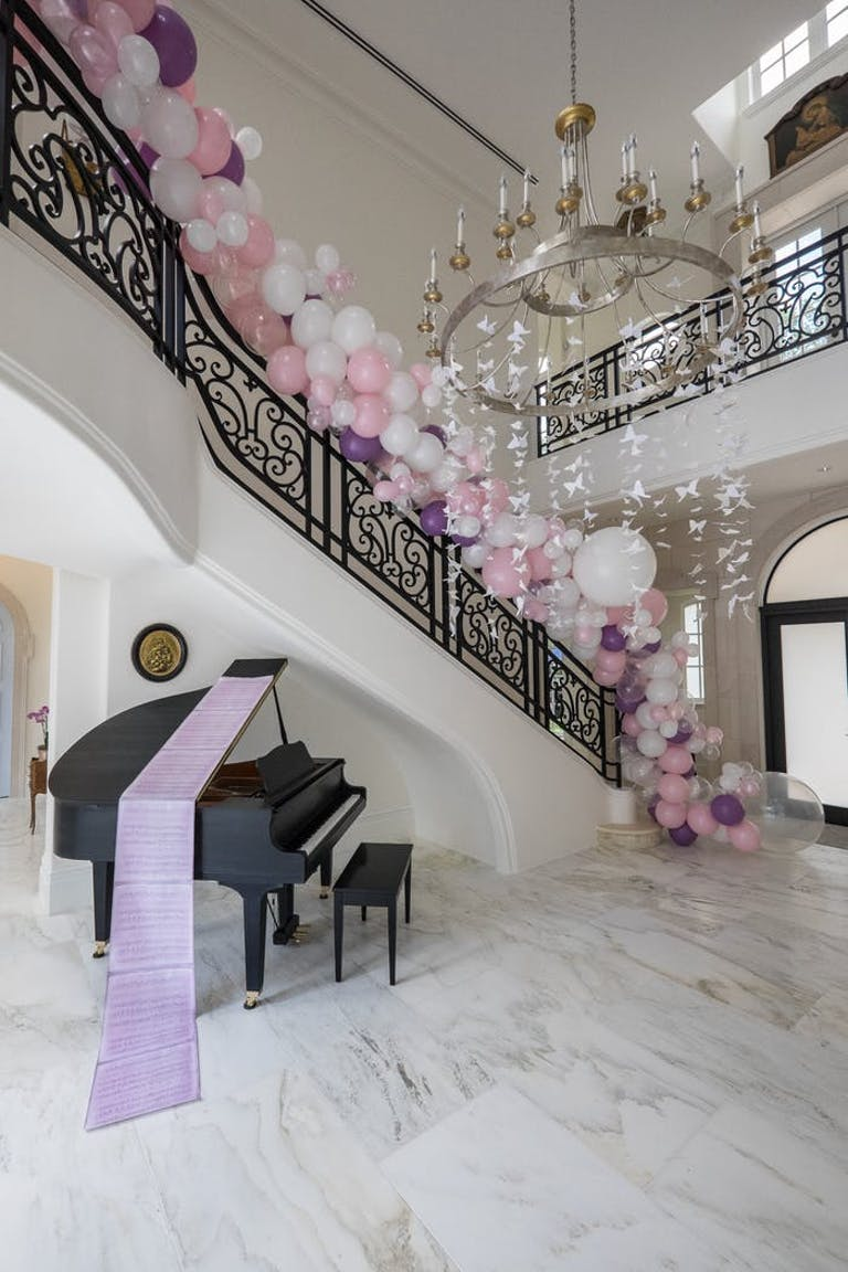 A grand staircase with a black piano underneath. A purple runner goes over the piano while pink and white balloons follow the rail up the stairs