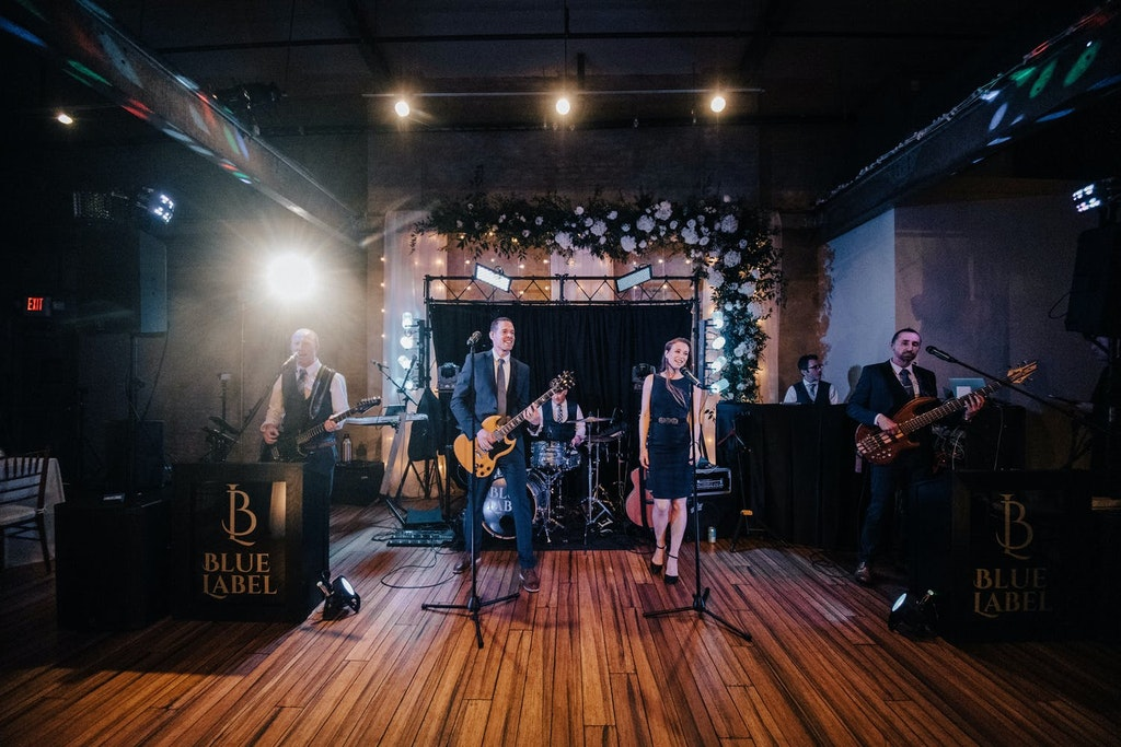 A six-piece band performs on a wooden stage in a raw industrial setting with a backdrop of greenery and white roses.