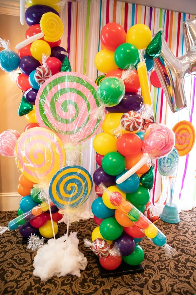 Colorful balloons intertwined with large candy elements