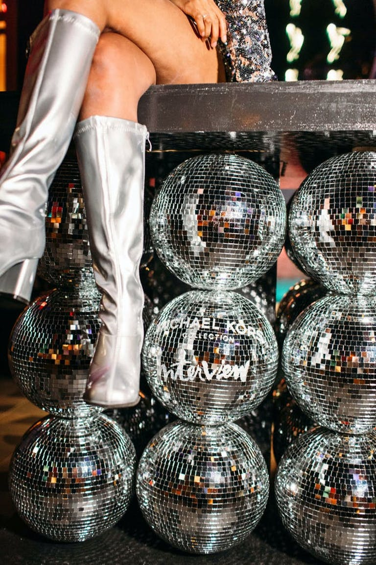 The legs of someone sitting on a bench with disco balls stacked as the legs | PartySlate