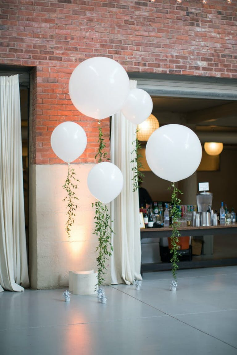 White circular balloons with greenery ribbons against a brick wall and a doorway to a larger table