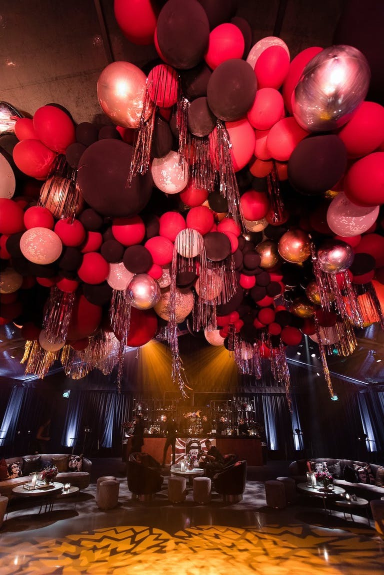 An image looking up at the ceiling with red, black and white balloons.