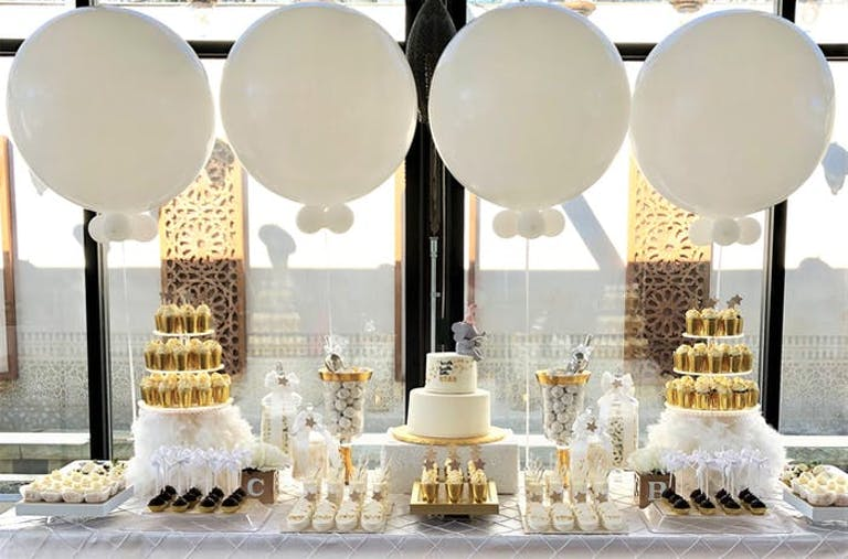 Four white balloons perched over the dessert table with cakes and treats in front of a window