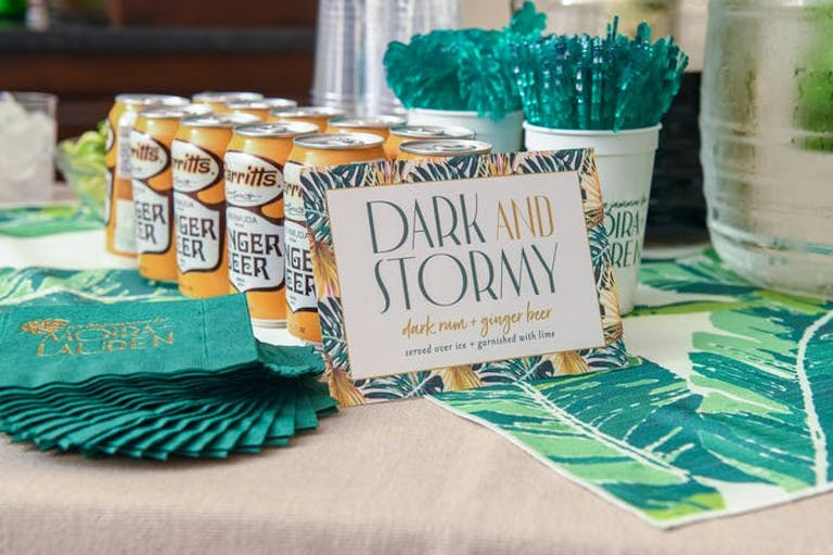3 lines of orange soda cans lined up with teal straws and cocktail napkins