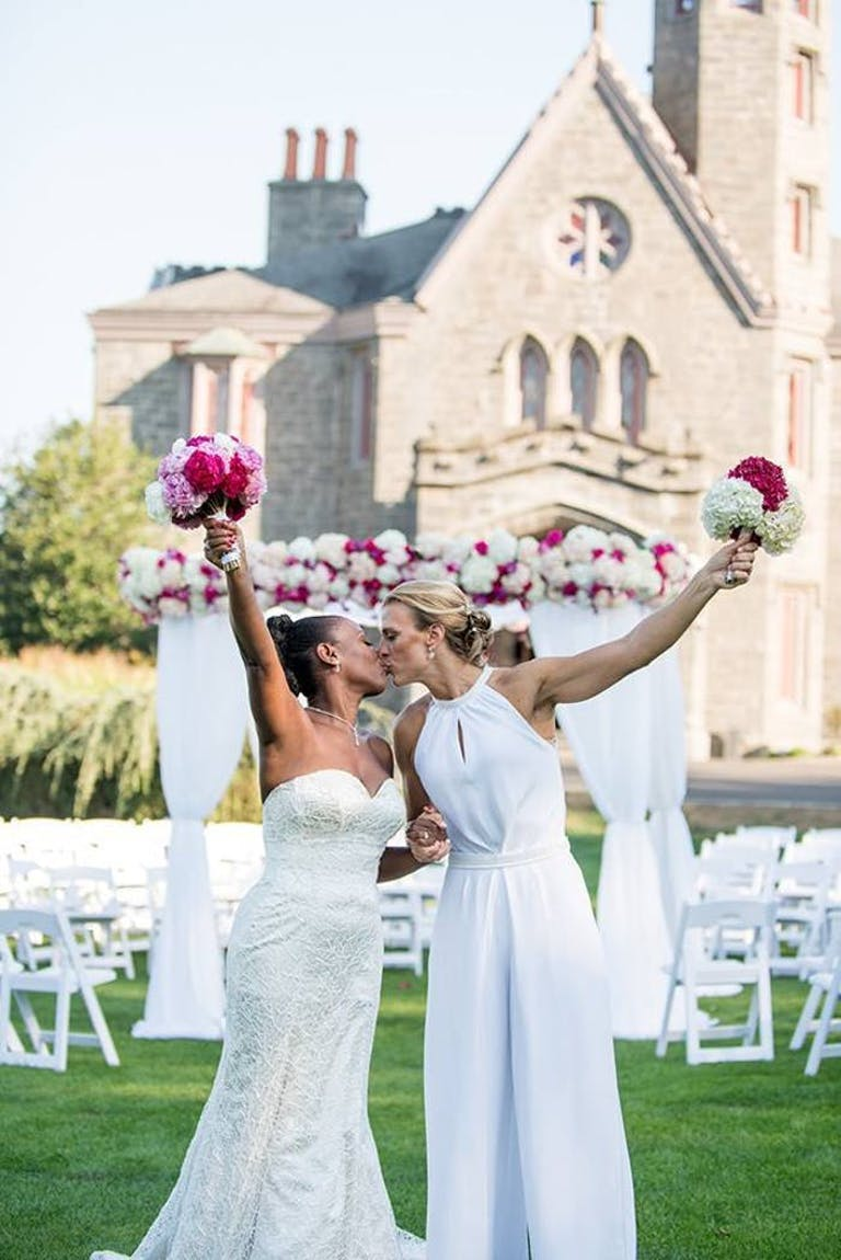 Two brides kiss and hold up their bouquets in front of their aisle and venue