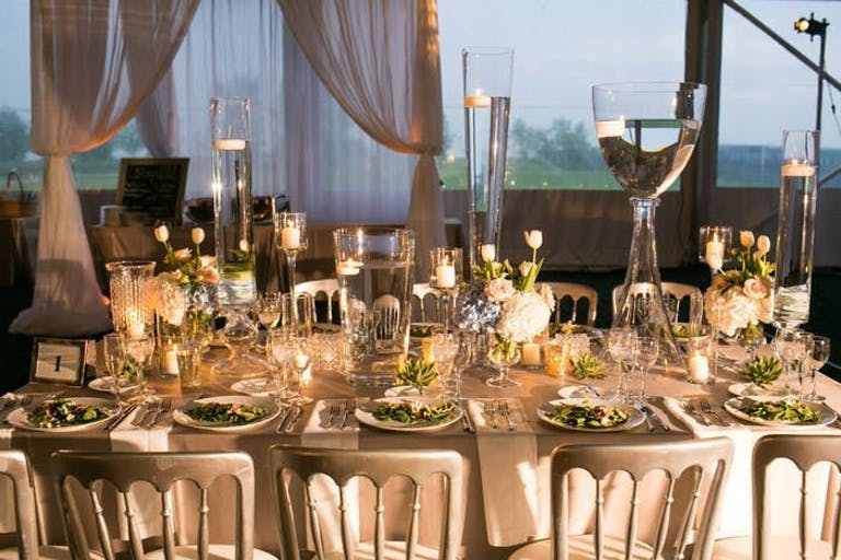 warmly lit table setting with cream drapery and lit candles