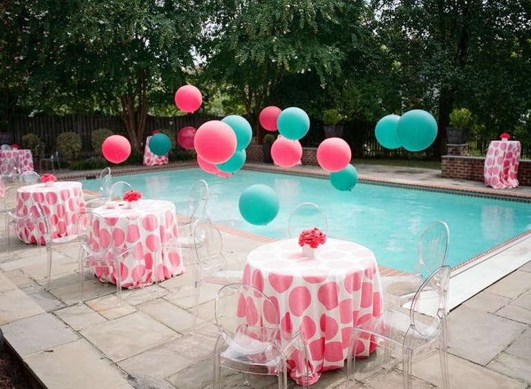 pink and white cocktail tables surrounding a blue pool. Pink and teal balloons hover above the pool