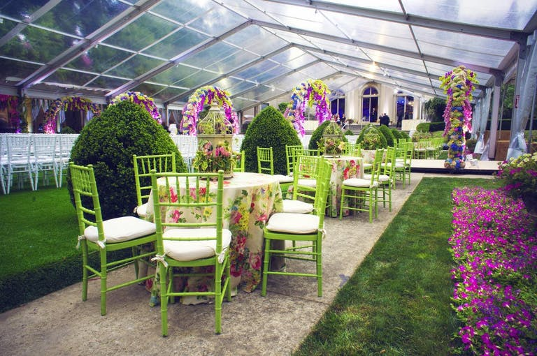 Tables and green chairs in a colorful indoor garden.