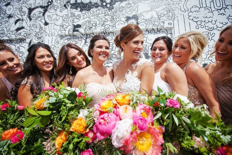 a bridal party stands in front of a black and white wall with colorful peonies and greenery