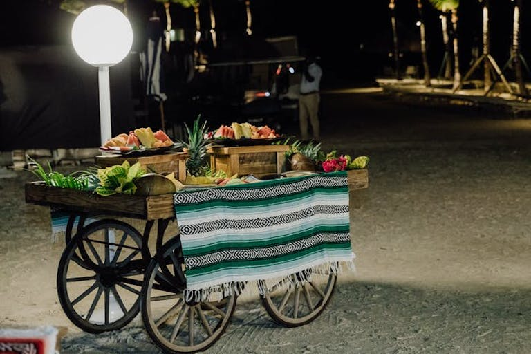 A cart with a blanket as a table cloth. Fruit in various fruit baskets sit on top.