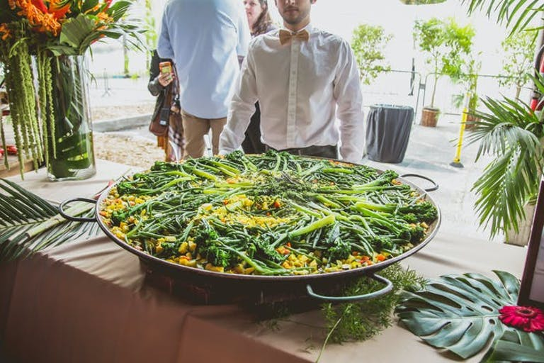 A paella with the server standing behind it