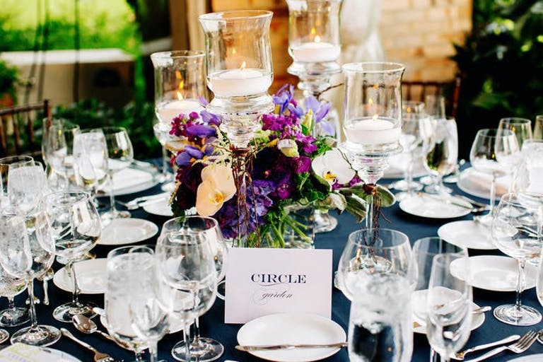purple flowers in the center of the table with glassware and candles surrounding.