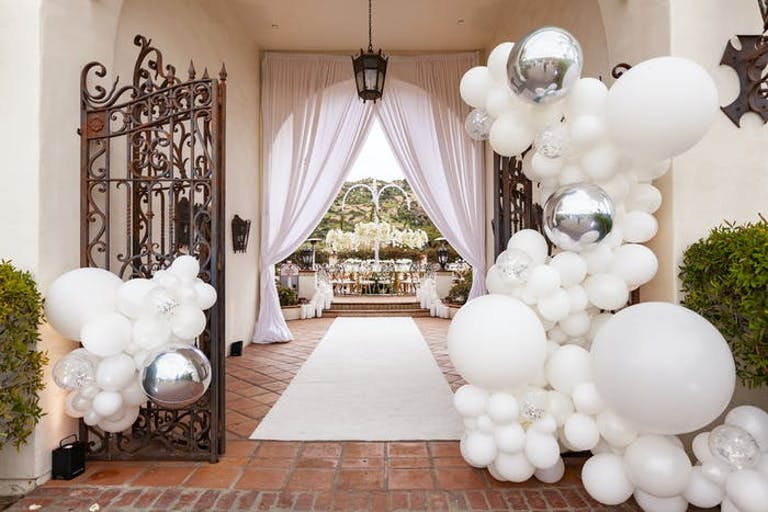 An entrance way with a decorative rod iron gate and terra-cotta tiled floors. White drapes at the end of the entrance and clusters of white balloons at the front