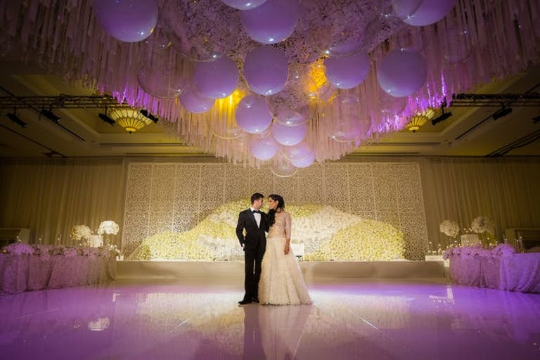 A couple standing on a dance floor. Purple and yellow lighting washes over the,,