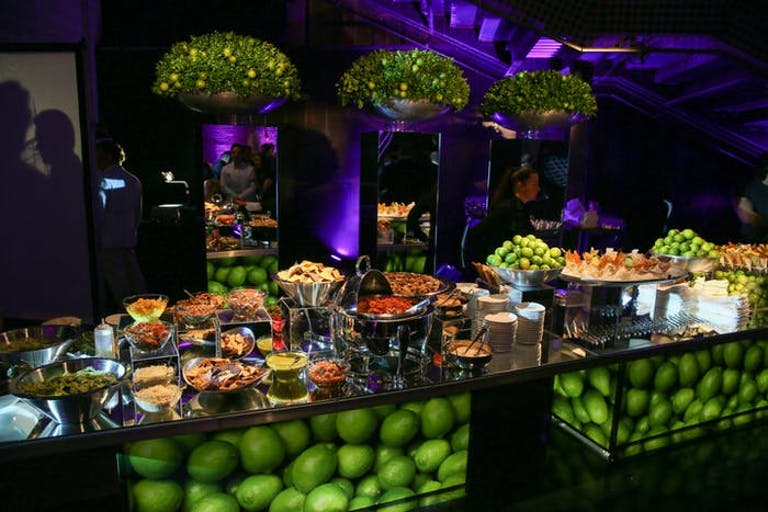 A lime centered catering station with dark and purple lighting