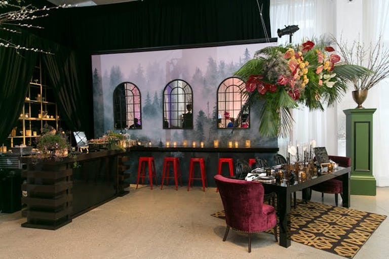 A room with a backdrop of windows and a night sky. A red chair sits at a narrow table with a tall centerpiece thats colorful and green. A bench sits along the backdrop with glowing candles