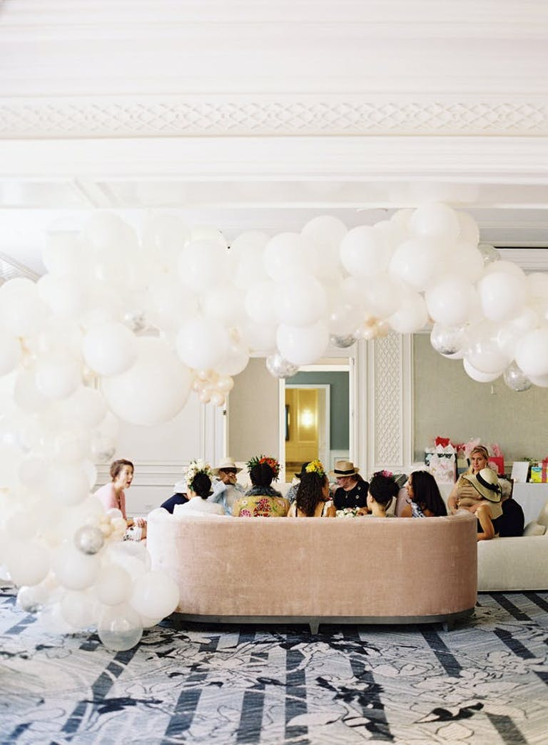 a taupe couch with people sitting on it. White balloons form a loose arch overhead