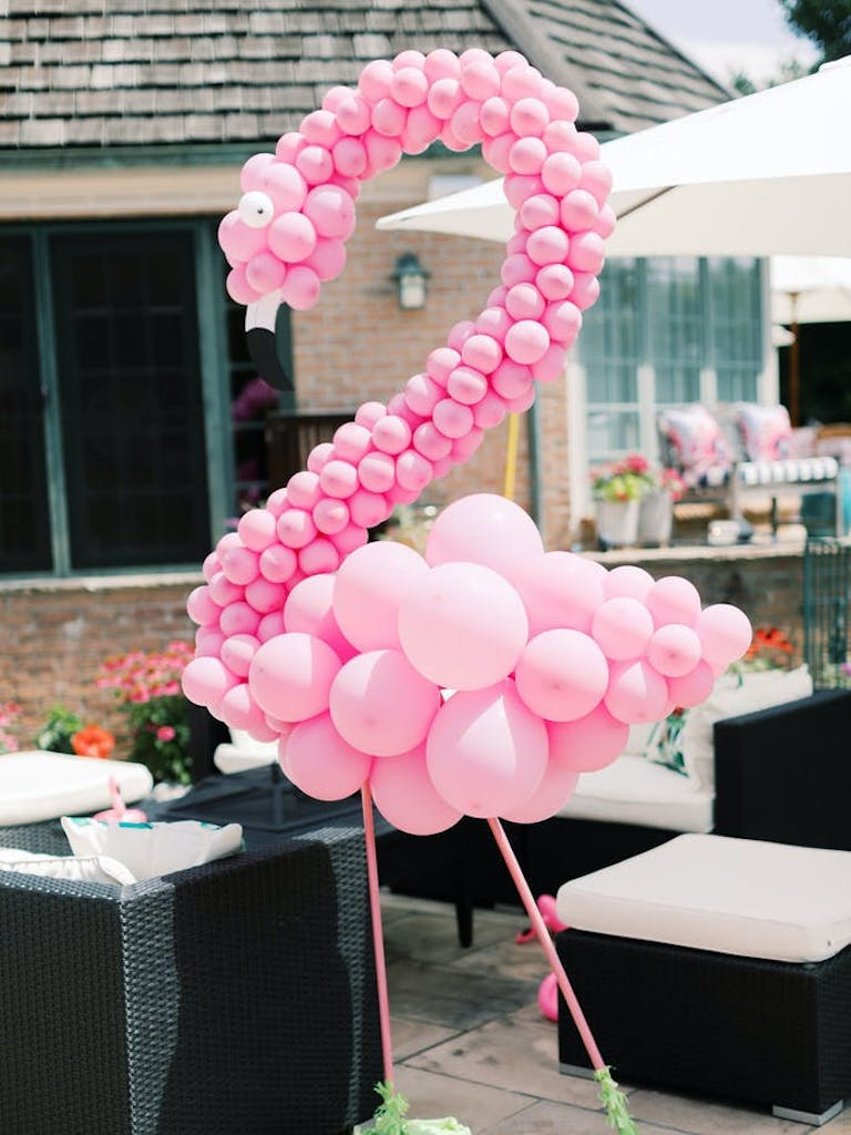 a pink flamingo made out of balloons in front of tables on the deck