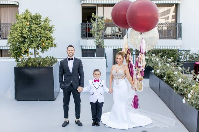 A bride and groom holding hands with their son, the bride holds two maroon balloons with pink tassels as the ribbon