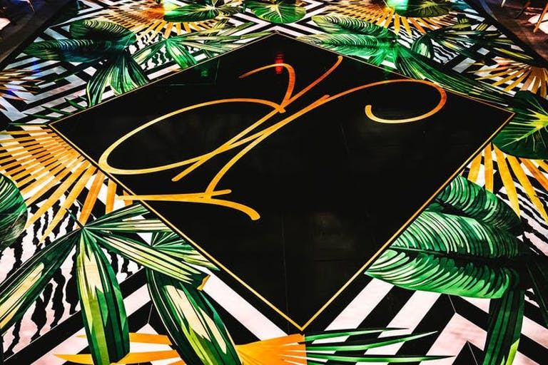 A black square dance floor with gold calligraphy through it. The outside of the dance floor is filled with black and white stripes and banana leaves