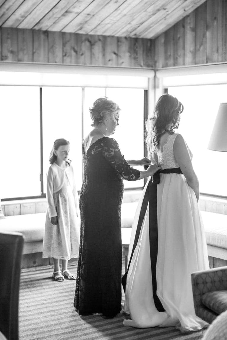 A mom ties the black bow of her daughter's wedding dress while a young girl in a white dress looks on.