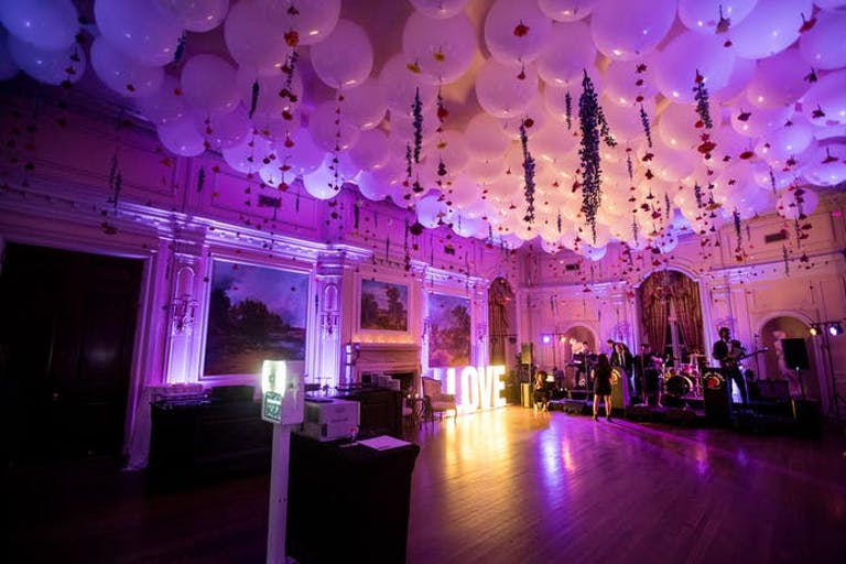 A large balroom dance floor lit up purple with white balloons covering the cieling