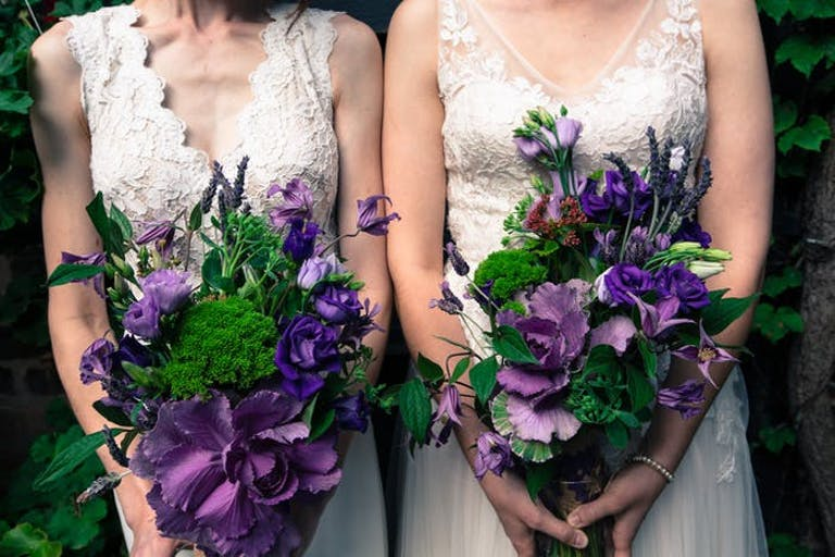 Two brides in white dresses holding purple and green bouquets