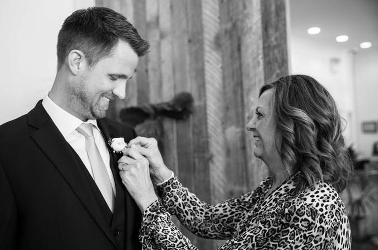 Mother pins a boutonnière to her son' tuxedo.