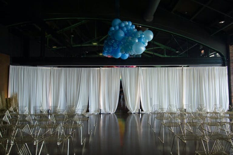 an industrial style warehouse with low white curtains separating the space, transparent chairs sit behind it and a cluster of blue balloons is above the curtain
