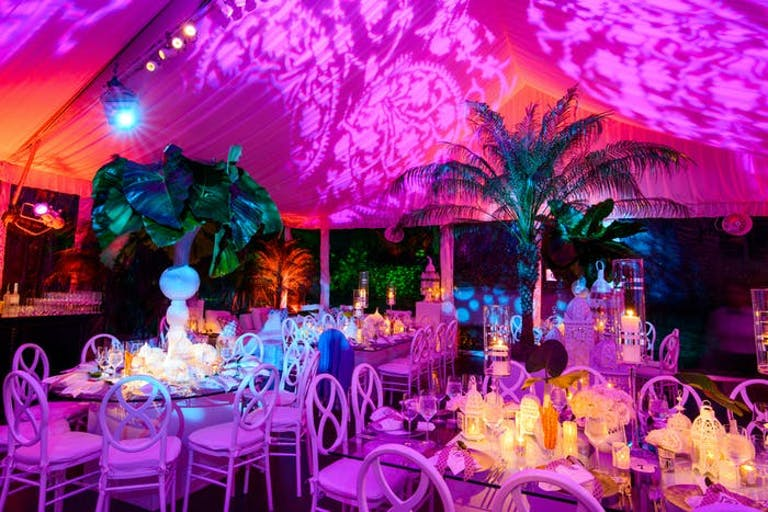 A tented room with a wash of pink lighting. Palm trees act as centerpieces and glowing candles surround them