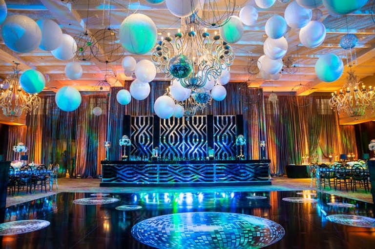 A black dance floor with disco balls printed on it. Multicolored balloons are over the dance floor with a stage in front | PartySlate