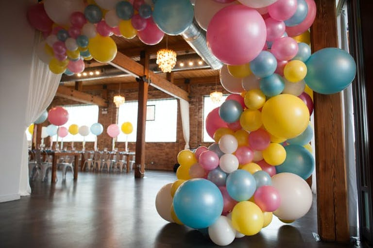 pink, blue and yellow balloons at the entrance. The background shows a long table in front of a window with the same color balloons