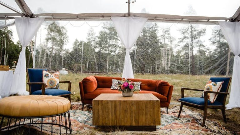 Burnt orange couch and chairs under a white linen canopy in a wooded area