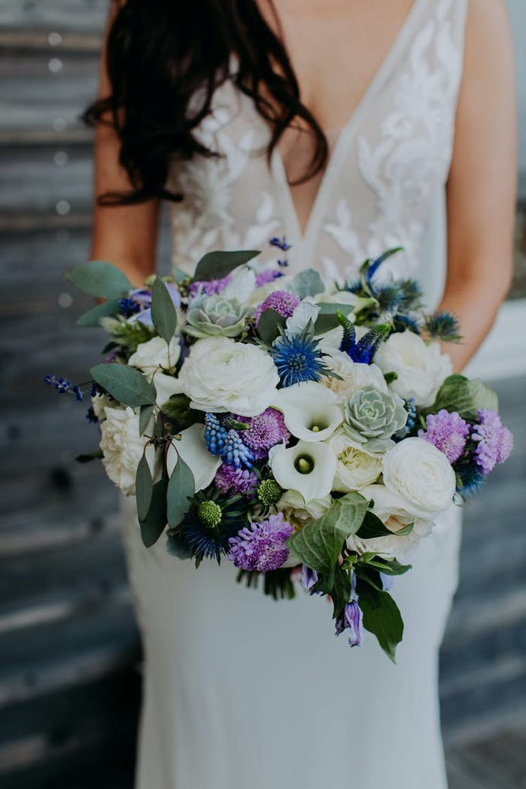 Bride standing holding her bouquet full of white, purple and blue florals