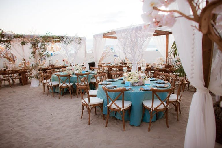 Sandy floor with round tables and blue linens. Lace canopies are draped over certain sections of tables