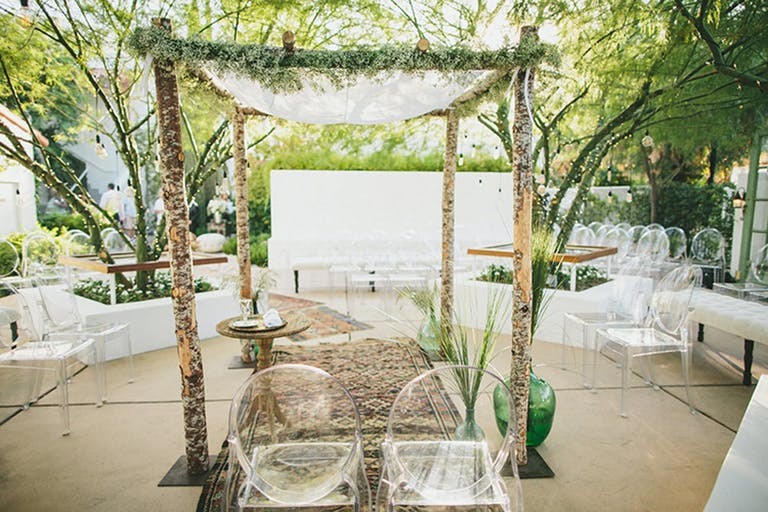 Outdoor wedding ceremony with lucite seating and rustic arch.