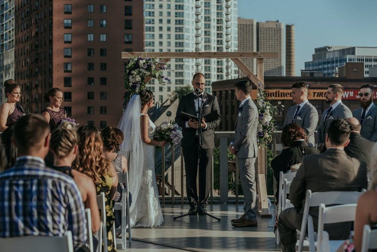 City rooftop wedding featuring rustic wedding arch.
