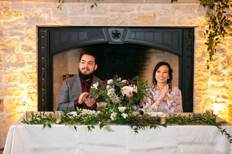 Couple sit at a sweetheart table in front of an uplit fireplace.