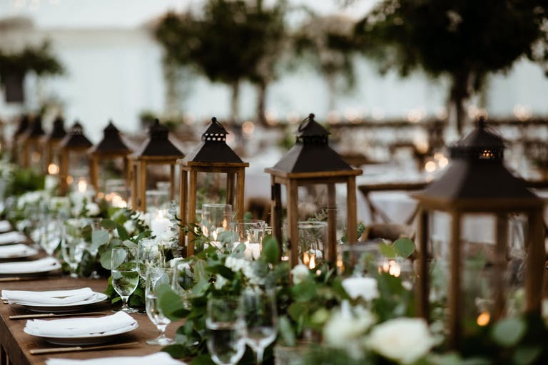 Rustic wedding reception table with lantern centerpieces.