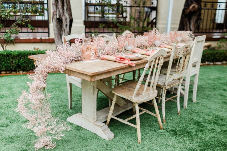 Intimate wedding reception table with pink baby's breath centerpieces.