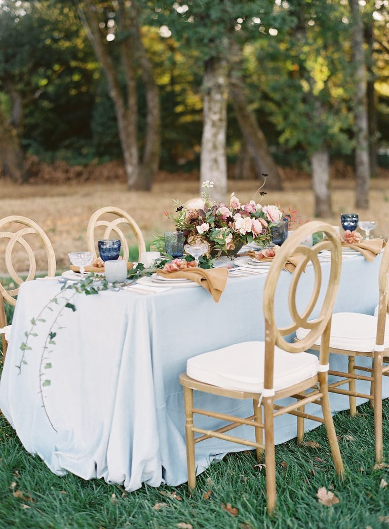 Small outdoor wedding reception table with rustic centerpieces.