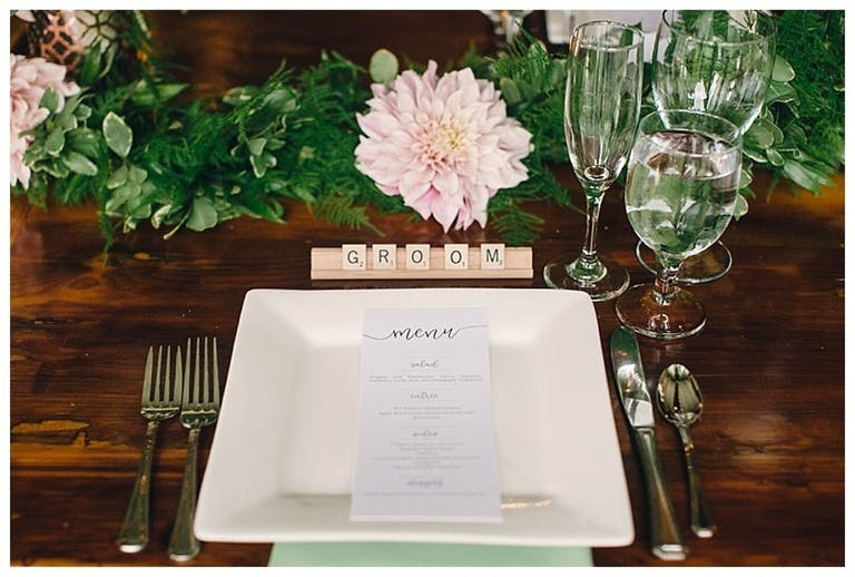 Wedding reception table with scrabble place card and pink flowers.
