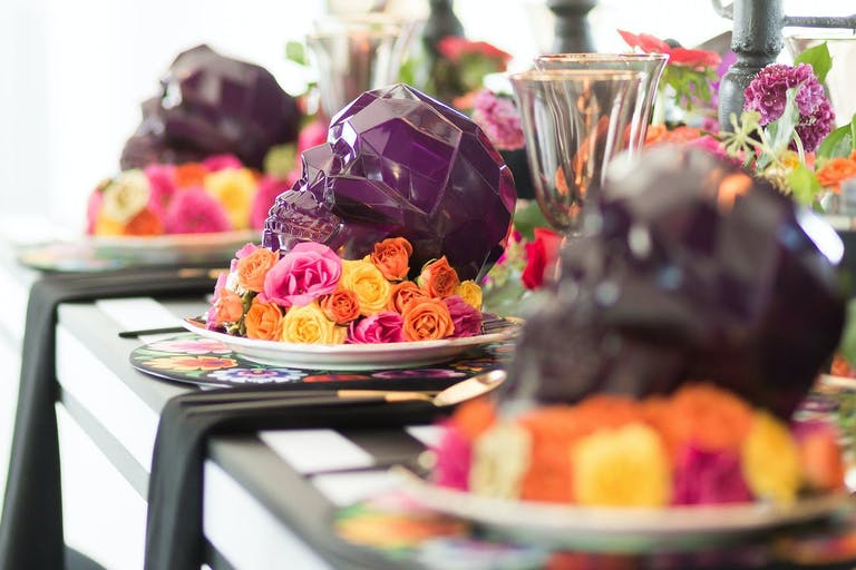 Halloween-themed corporate dinner party with purple skull decorations.