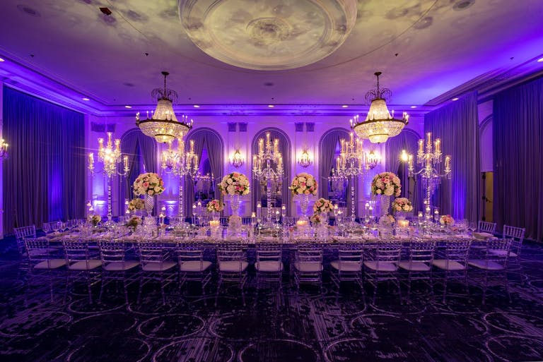 Corporate dinner party at ballroom with dramatic mood lighting.