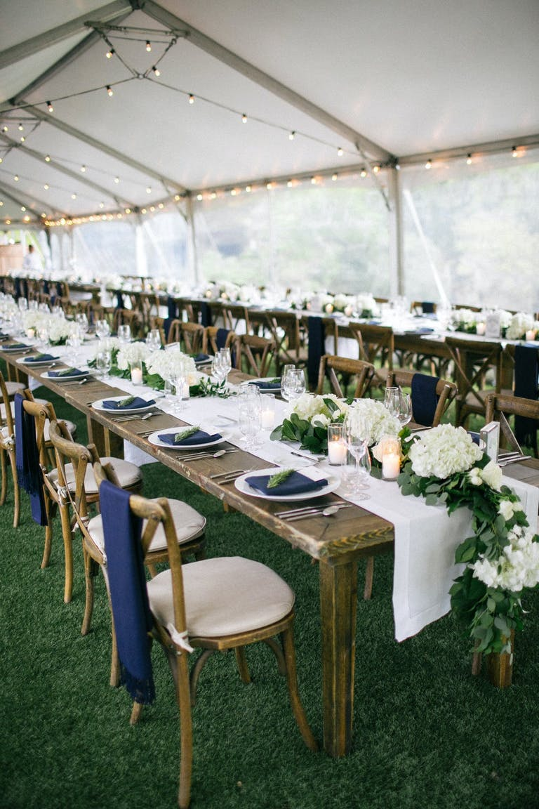 Wedding reception tent and tables with blue chair décor.