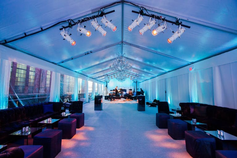 Tented corporate dinner party with blue uplighting.