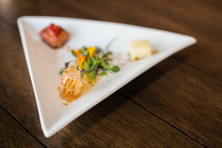Corporate dinner party with artistic food on triangle plates.