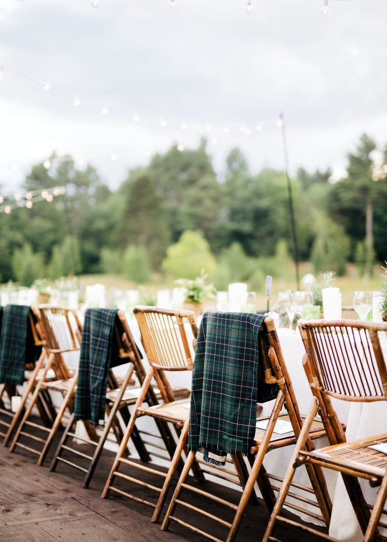 Wedding reception table seating with flannel throw blankets.