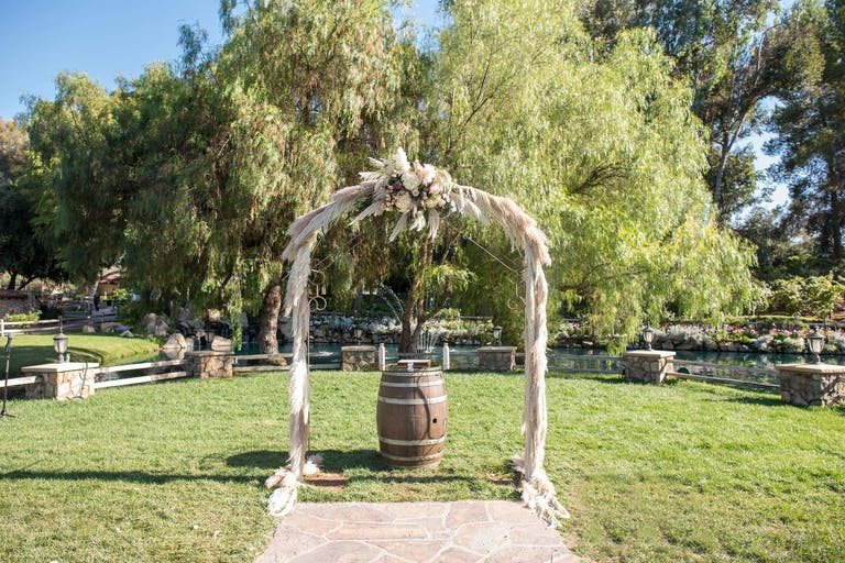 Rustic wedding arch with pampas grass and a rustic wine barrel.