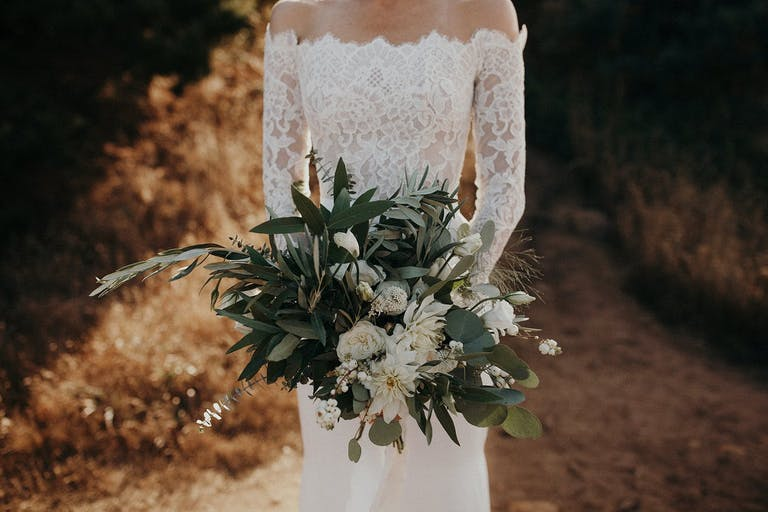 Rustic wedding bouquet with greenery and white blooms.